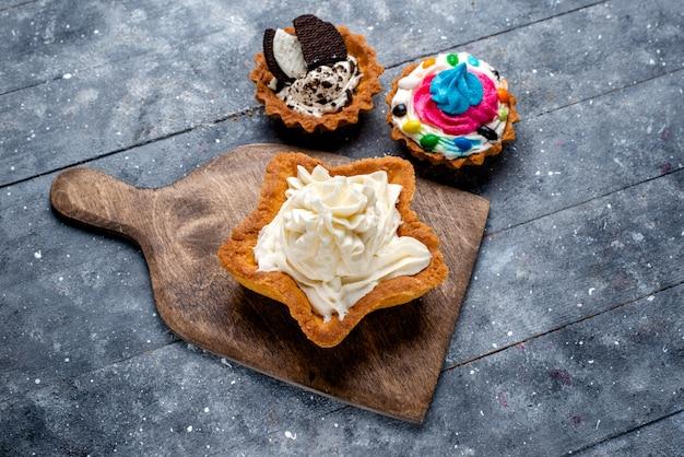 Widok z góry pyszne kremowe ciasto w kształcie gwiazdy z ciasteczkami na lekkim stole ciasto biszkoptowe krem słodka herbata