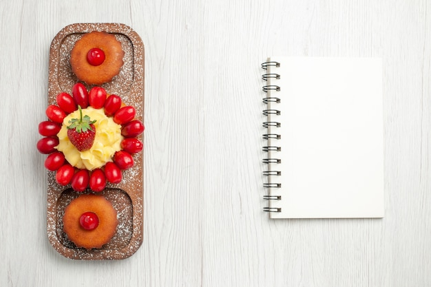 Widok z góry pyszne kremowe ciasto z ciastami na białym biurku