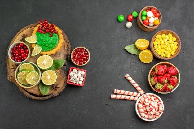 Widok z góry pyszne kremowe ciasto z cukierkami i owocami na ciemnym tle słodkie ciasteczko