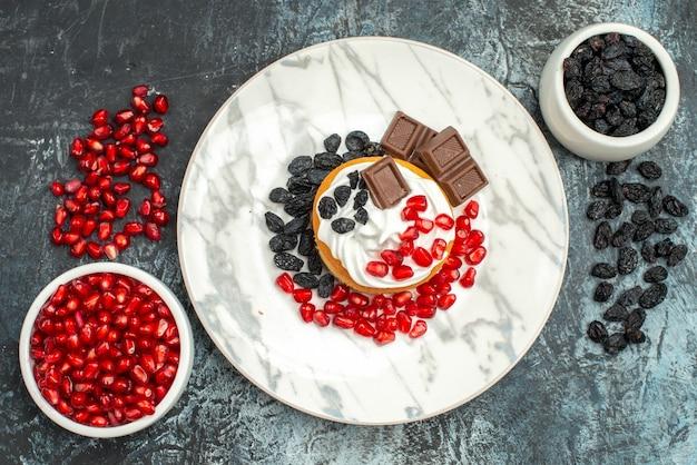 Widok z góry pyszne kremowe ciasto z czekoladowymi granatami i rodzynkami na jasno-ciemnym tle