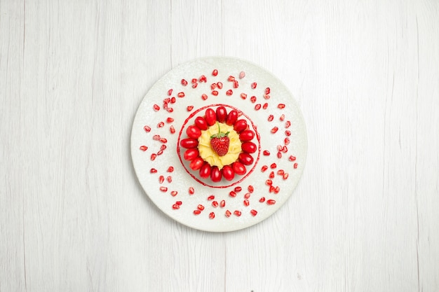 Widok z góry pyszne kremowe ciasto z dereniami na białym biurku