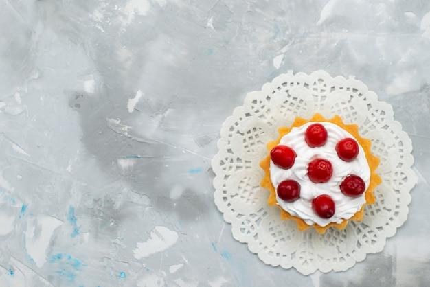 Widok z góry pyszne kremowe ciasto z kremem i czerwonymi owocami na szarej powierzchni biszkoptowe słodkie ciasto cukrowe owocowe