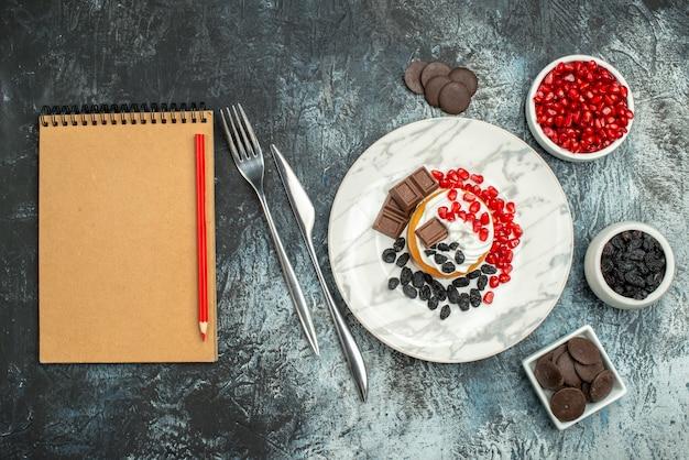 Widok z góry pyszne kremowe ciasto z rodzynkami i filiżanką herbaty na jasno-ciemnym tle