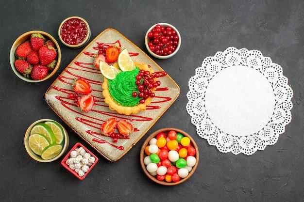 Widok z góry pyszne kremowe ciasto z truskawkami na ciemnym biurku słodka herbata deserowa z cukrem