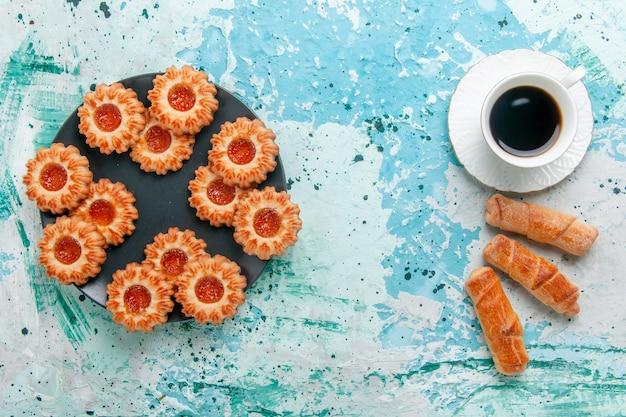 Widok z góry pyszne małe ciasteczka z bułeczkami i filiżanką kawy na niebieskim biurku herbatniki herbatniki słodki cukier kolor herbaty