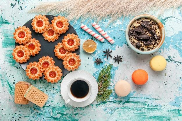 Widok z góry pyszne małe ciasteczka z filiżanką kawy i goframi na niebieskiej powierzchni herbatniki herbatniki słodka herbata kolor cukru