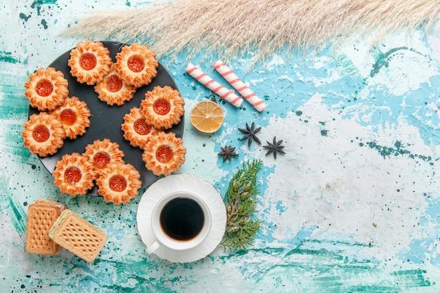 Widok z góry pyszne małe ciasteczka z goframi i filiżanką kawy na niebieskim biurku ciastko herbatnikowe słodki cukier