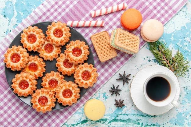 Widok z góry pyszne małe ciasteczka z kawą z dżemem pomarańczowym i goframi na niebieskiej powierzchni herbatniki herbatniki słodki cukier kolor herbaty