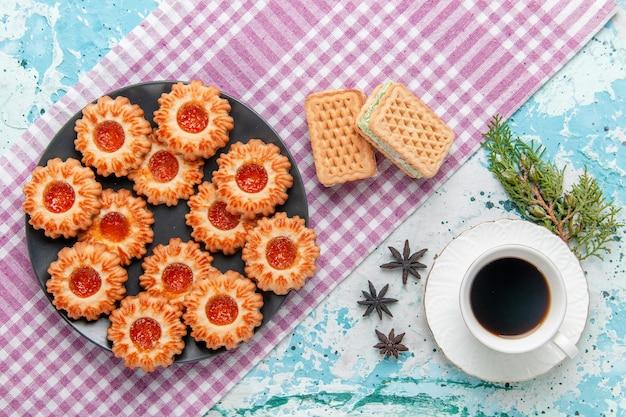 Widok z góry pyszne małe ciasteczka z kawą z dżemem pomarańczowym i goframi na niebieskim biurku herbatniki herbatniki słodki cukier kolor herbaty