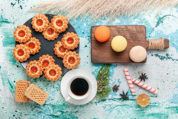 Widok z góry pyszne małe ciasteczka z makaronikami waflowymi i filiżanką kawy na niebieskim biurku herbatniki herbatniki słodki cukier kolor herbaty