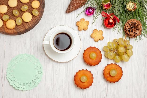 Widok z góry pyszne małe ciastka z winogronami i filiżanką herbaty na jasnym białym biurku