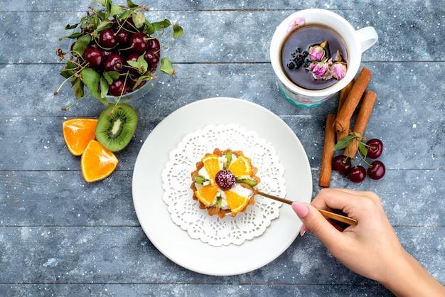 Widok z góry pyszne małe ciasto ze śmietaną i świeżymi pokrojonymi owocami wraz z herbatą cynamonową na szaro-niebieskim biurku ciasto owocowe herbatniki herbaciane