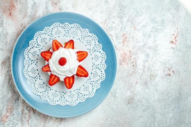Widok z góry pyszne małe ciasto ze śmietaną i truskawkami na białej przestrzeni
