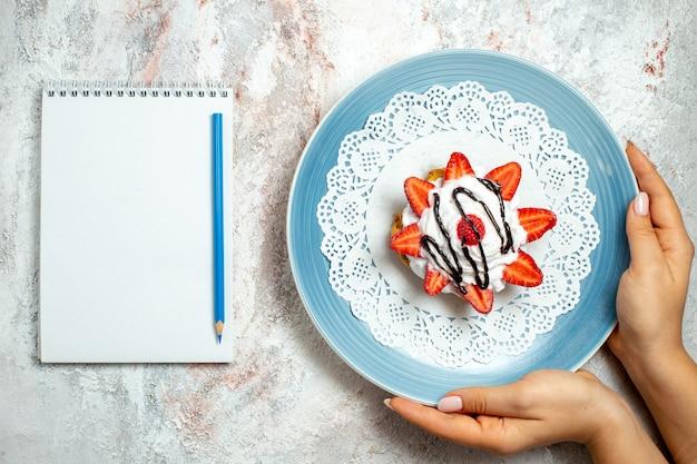 Widok z góry pyszne małe ciasto ze śmietaną i truskawkami na białym tle