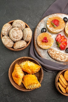 Widok z góry pyszne naleśniki z owocami i słodkimi ciastami w ciemności