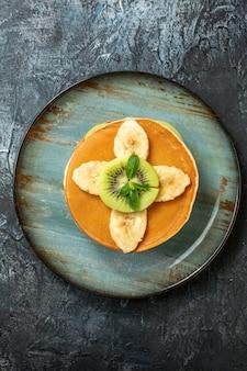 Widok z góry pyszne naleśniki z pokrojonymi kiwi i bananami na ciemnej powierzchni owoce słodki deser kolor ciasto cukier