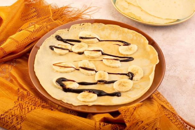 Widok z góry pyszne naleśniki zaprojektowane z czekoladą i bananami wewnątrz brązowego okrągłego talerza na różowym stole deserowym