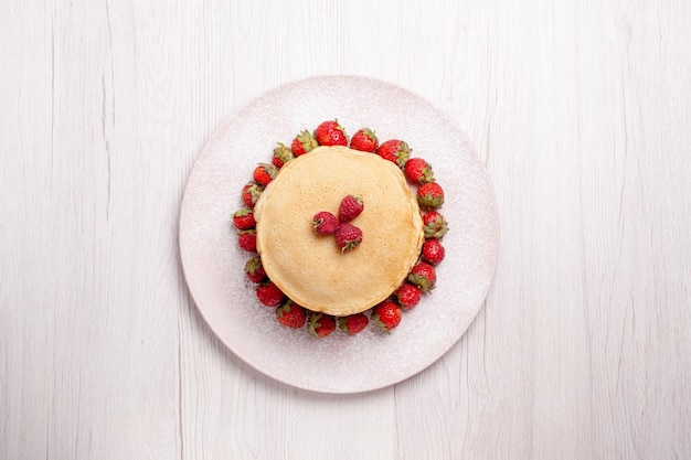 Widok z góry pyszne naleśniki ze świeżymi czerwonymi truskawkami na białym tle ciasto owocowe ciasto jagodowe słodki biszkoptowy cukier