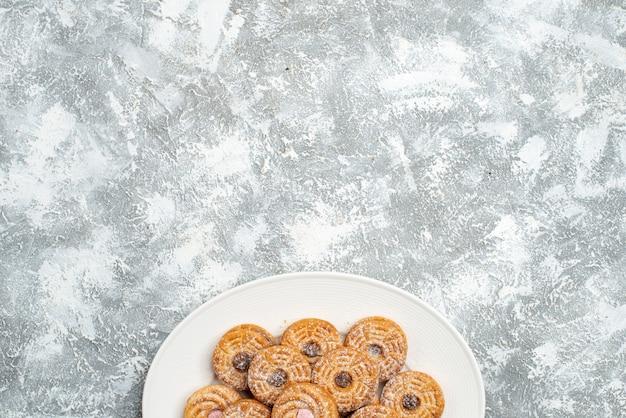 Widok z góry pyszne okrągłe ciastka wewnątrz płyty na białej przestrzeni