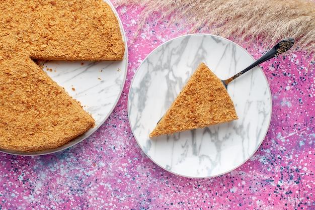Widok z góry pyszne okrągłe ciasto wewnątrz talerza na jasnoróżowym biurku ciasto biszkoptowe słodkie wypieki