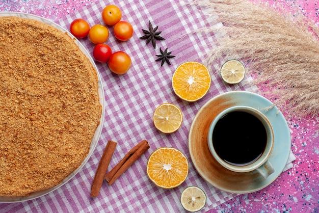 Widok z góry pyszne okrągłe ciasto wewnątrz talerza z owocami i herbatą na jasnoróżowym biurku ciasto biszkoptowe słodkie wypieki