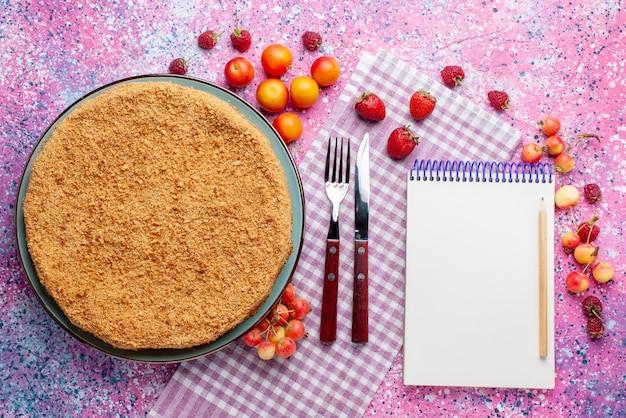 Widok z góry pyszne okrągłe ciasto wewnątrz talerza z owocami na jasnoróżowym biurku ciasto biszkoptowe słodki cukier do pieczenia