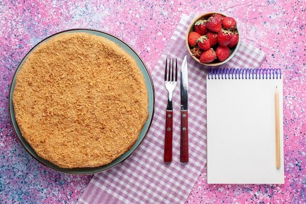 Widok z góry pyszne okrągłe ciasto wewnątrz talerza z truskawkami na jasnoróżowym biurku ciasto biszkoptowe słodki cukier do pieczenia