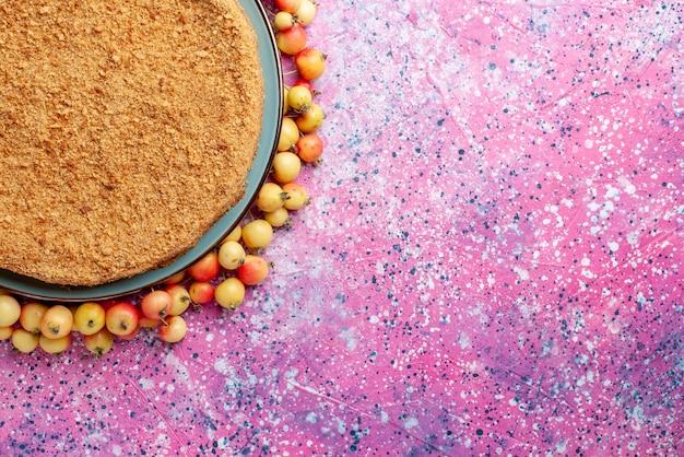 Widok z góry pyszne okrągłe ciasto wewnątrz talerza z wyłożonymi czereśniami na jasnoróżowym biurku ciasto biszkoptowe cukier słodki