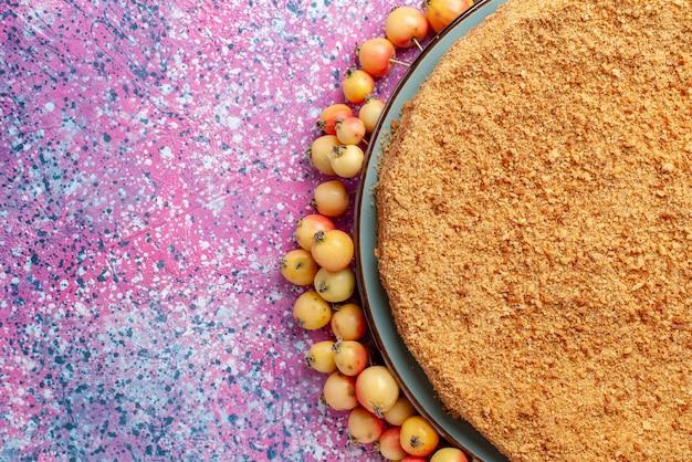 Widok z góry pyszne okrągłe ciasto wewnątrz talerza z wyłożonymi czereśniami na jasnoróżowym biurku ciasto biszkoptowe słodkie wypieki