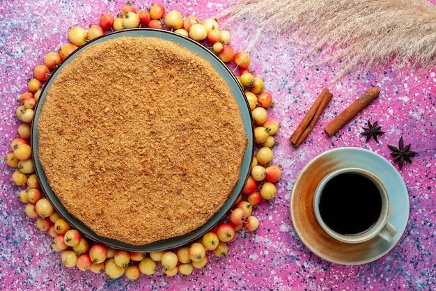 Widok z góry pyszne okrągłe ciasto wewnątrz talerza z wyściełanymi czereśniami i herbatą na jasnoróżowym herbatniku na biurku