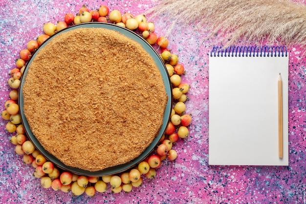 Widok z góry pyszne okrągłe ciasto wewnątrz talerza z wyściełanymi czereśniami i notatnikiem na jasnoróżowym biurku ciasto biszkoptowe słodki cukier do pieczenia