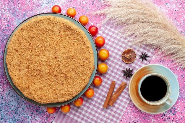 Widok z góry pyszne okrągłe ciasto wewnątrz talerza ze śliwkami wiśniowymi i herbatą na różowym biurku ciasto biszkoptowe słodki cukier do pieczenia