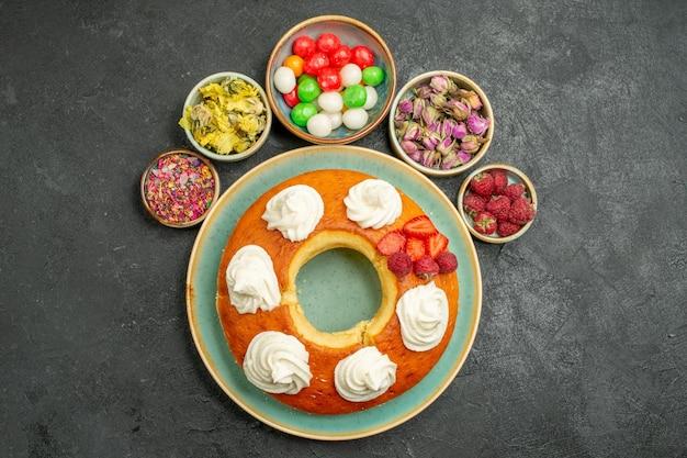 Widok z góry pyszne okrągłe ciasto z cukierkami na szarym tle ciastko ciastko ciastko ciasto słodka herbata