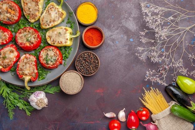Widok z góry pyszne papryki smaczne gotowane danie z mięsem i przyprawami na ciemnej podłodze danie pieprz kolacja pikantne jedzenie