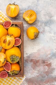 Widok z góry pyszne persimmons i cięte figi w drewnianym pudełku na nagim tle