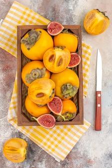Widok z góry pyszne persimmons i cięte figi w drewnianym pudełku żółty ręcznik kuchenny nóż na nagim tle