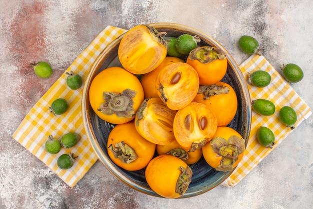 Widok z góry pyszne persimmons w misce na ręczniku feykhoa na nagim tle