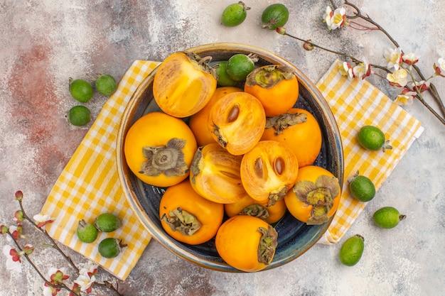 Widok z góry pyszne persimmons w misce na ręczniku kuchennym na nagim tle