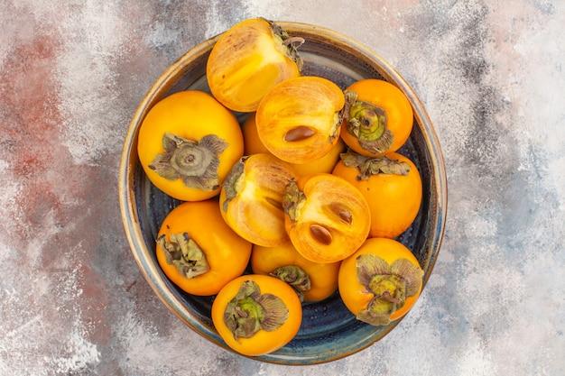Widok z góry pyszne persimmons w okrągłym drewnianym pudełku na nagim tle