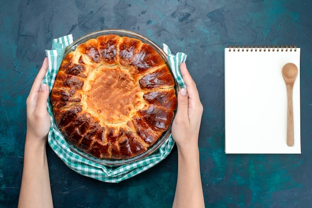 Widok z góry pyszne pieczone ciasto okrągłe uformowane na słodko wewnątrz szklanej patelni na jasnoniebieskim biurku.