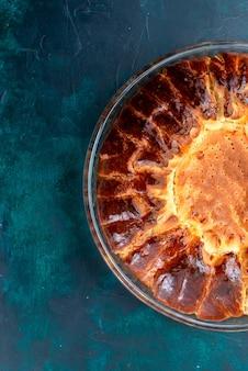 Widok z góry pyszne pieczone ciasto okrągłe utworzone słodkie wewnątrz szklanej patelni na jasnoniebieskim tle.