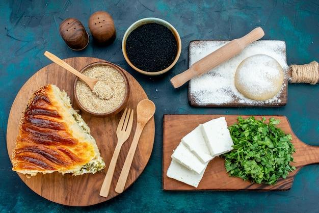 Widok z góry pyszne pieczone ciasto w plastrach z nadzieniem z zieleniny ze świeżym białym serem i zieleniną na ciemnym tle.