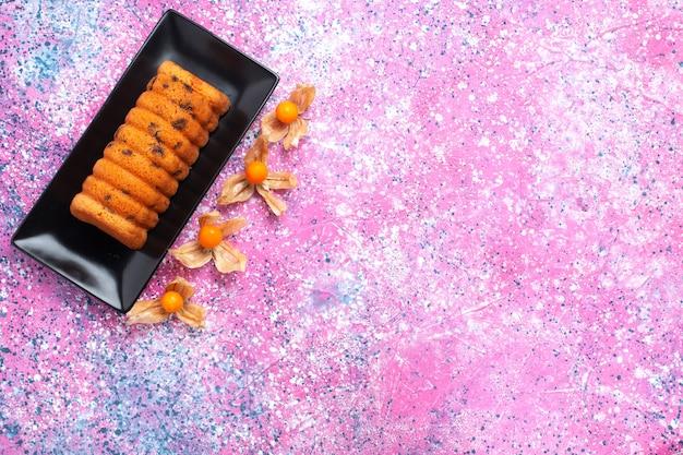 Widok z góry pyszne pieczone ciasto wewnątrz czarnej formy do ciasta z fizalizami na różowym biurku.