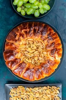 Widok z góry pyszne pieczone ciasto z rodzynkami i świeżymi zielonymi winogronami na ciemnoniebieskiej powierzchni ciasto ciasto cukier słodkie ciasto biszkoptowe