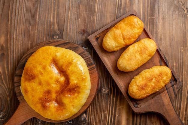 Widok z góry pyszne pieczone ciasto z tłuczonymi ziemniakami w środku i ciepłe bułeczki na drewnianym biurku