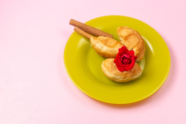 Widok z góry pyszne pieczone rogaliki z nadzieniem owocowym z cynamonem wewnątrz zielonego talerza na różowym tle