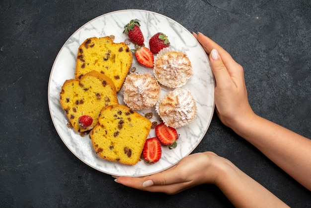 Widok z góry pyszne plasterki ciasta ze świeżymi czerwonymi truskawkami i ciasteczkami na szarej powierzchni