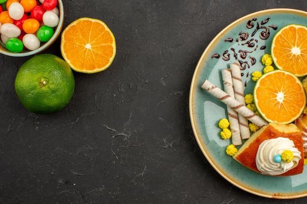 Widok z góry pyszne plastry ciasta z ciasteczkami fajkowymi i świeżymi pokrojonymi mandarynkami na ciemnym tle ciasto owocowe ciasto słodkie herbatniki