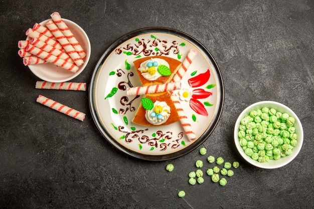 Widok z góry pyszne plastry ciasta z cukierkami na szaro