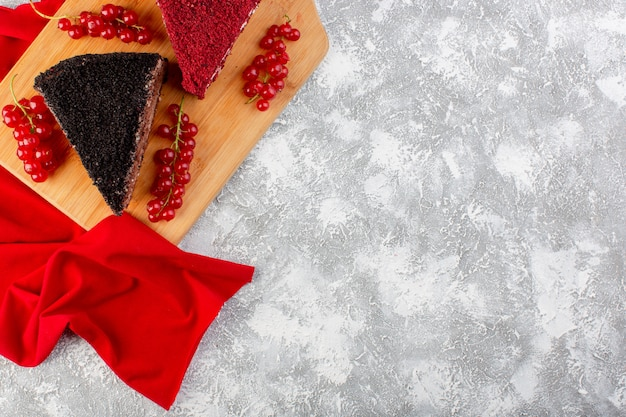 Widok z góry pyszne plastry ciasta z kremową czekoladą i owocami na drewnianym biurku z czerwoną bibułką biszkoptowe słodkie